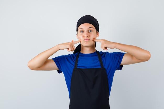 Giovane cuoco in maglietta, grembiule che preme le dita sulle fossette e sembra annoiato, vista frontale.