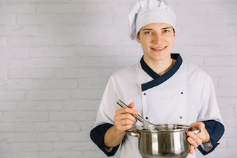Young cook whipping something in small pot with whisk