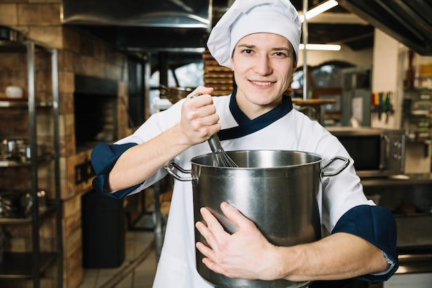 Young cook whipping something in pot with whisk