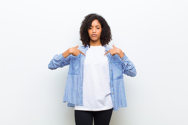 Young cool african american woman looking proud, positive and casual pointing to chest with both hands