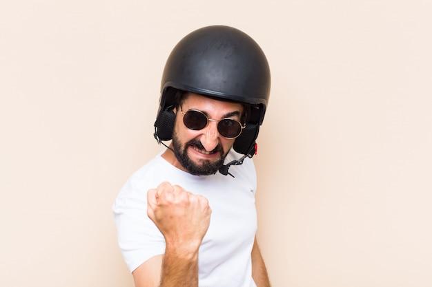 若いクールなひげを生やした男のヘルメットで怒った表情