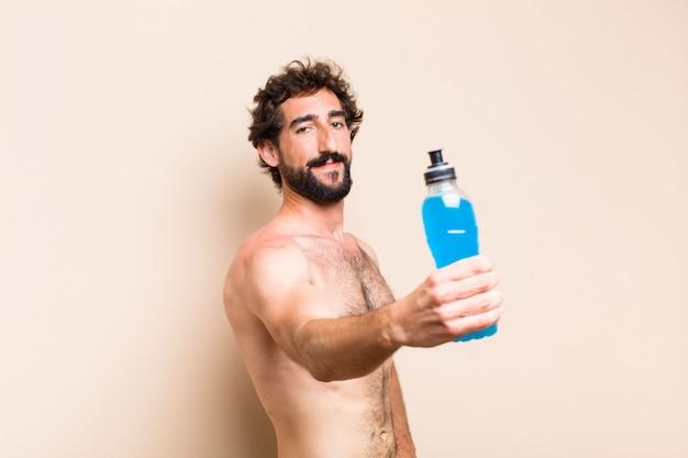 若いクールなひげを生やした男がエネルギードリンクフィットネスの概念を飲む