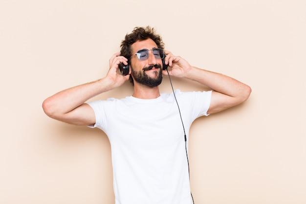 ヘッドフォンで音楽を聴く若いクールなひげを生やした男