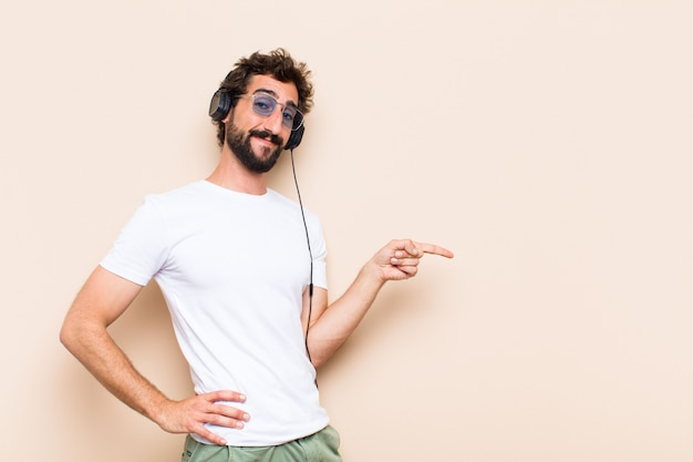 Young cool bearded man pointing to the side  listening music with a headphones