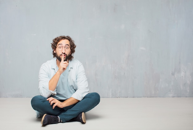 Young cool bearded man sitting on the floor. grunge wall background