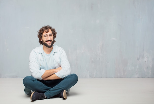 若い、ひげそり、床に座っている男。壁紙の背景