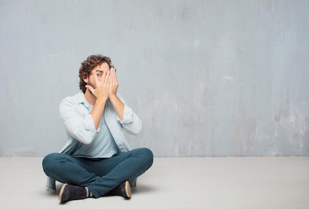 수염 난된 젊은이 바닥에 앉아. 그런 지 벽 배경