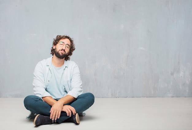 Молодой холодный бородатый человек, сидящий на полу. гранж фон стены