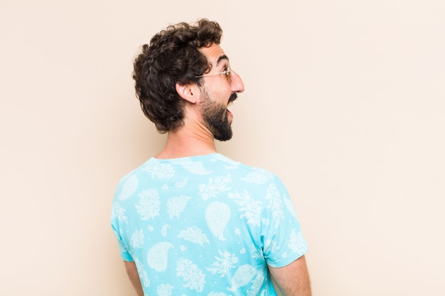 Young cool bearded man surprised and looking to the side