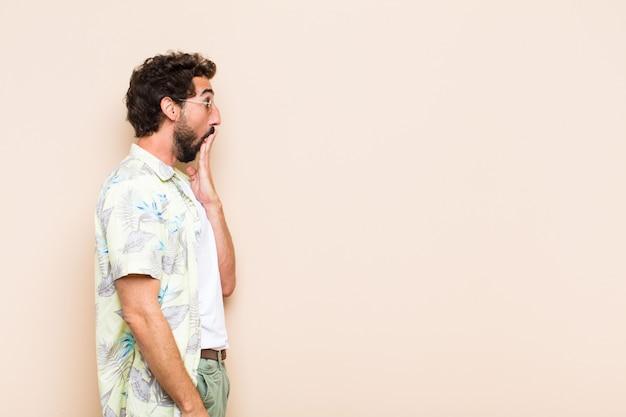 Молодой спокойный бородатый мужчина удивлен или шокирован и смотрит в сторону