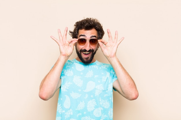 Young cool bearded man surprised with sun glasses.