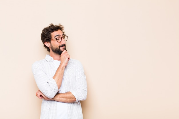 Young cool bearded man thinking or doubting expression