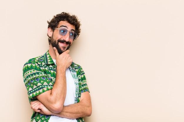 Молодой спокойный бородатый мужчина думает или выбирает