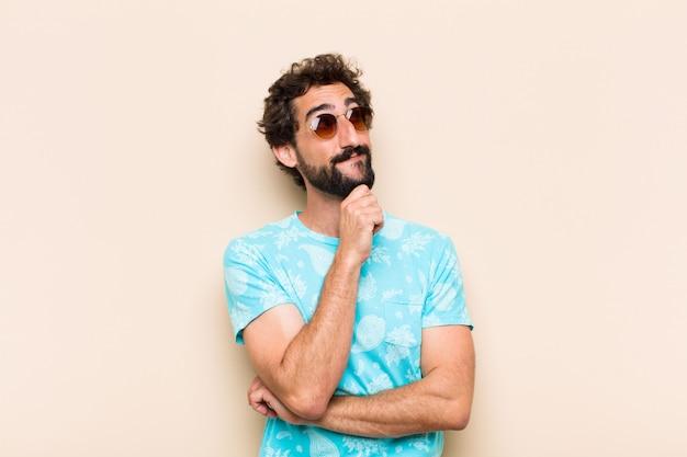 Молодой спокойный бородатый мужчина думает