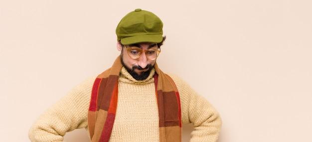 Молодой крутой бородатый мужчина с тупым, сумасшедшим, удивленным выражением лица, надутыми щеками, чувствуя себя набитым, толстым и полным еды