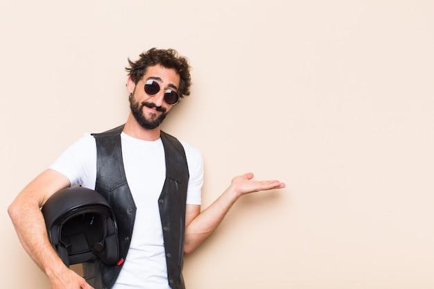 Молодой крутой бородатый мужчина со шлемом, указывающим в сторону