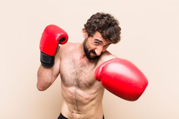 若いクールなひげを生やしたボクシンググローブとフィットネスの概念の戦い