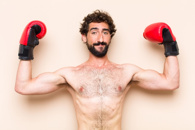Young cool bearded man with boxing gloves and fighting fitness concept