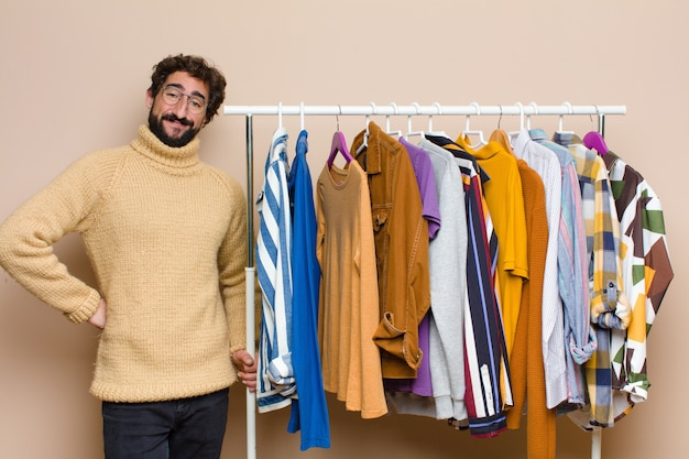 Young cool bearded man with clothes against flat wall