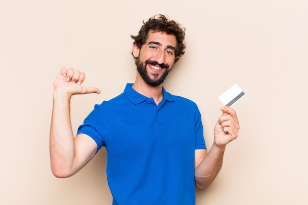 Young cool bearded man with a credit card