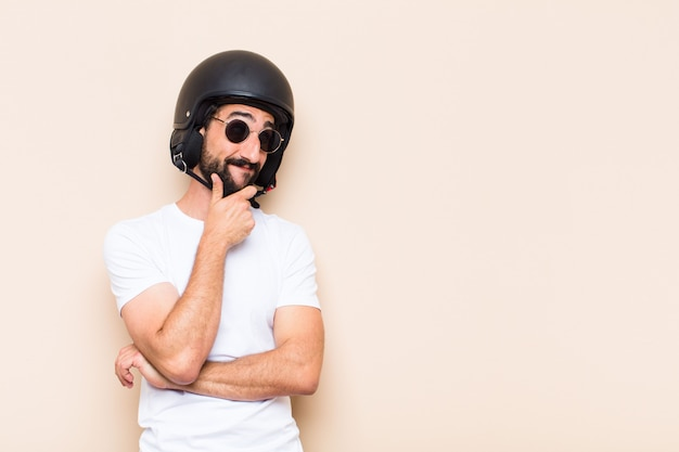 Young cool bearded man with a helmet thinking