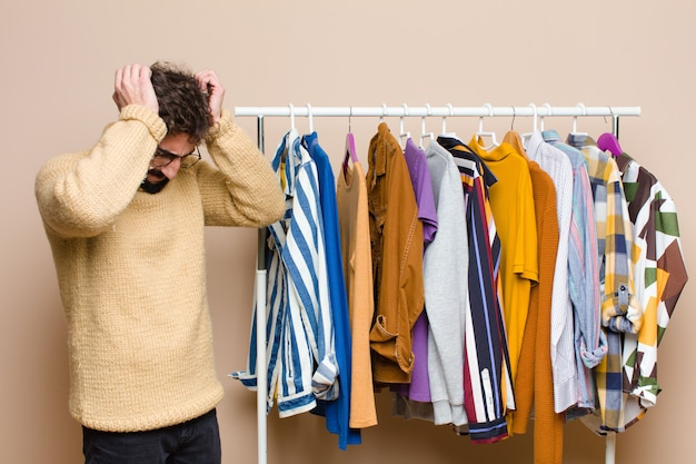 Young cool berded man with clothes against flat wall