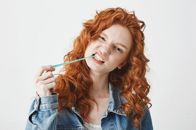 白い背景の上のジーンズのジャケットのチューインガムで若いクールな残忍な赤毛の女の子。