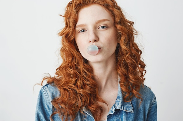 Young cool brutal redhead girl in jean jacket chewing gum over white background.