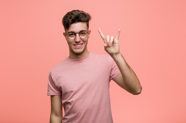 Young cool caucasian man showing a horns gesture as a revolution concept.
