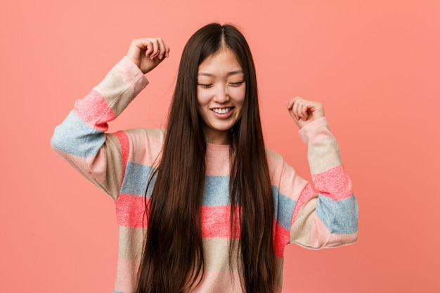 Young cool chinese woman celebrating a special day, jumps and raising arms with energy.