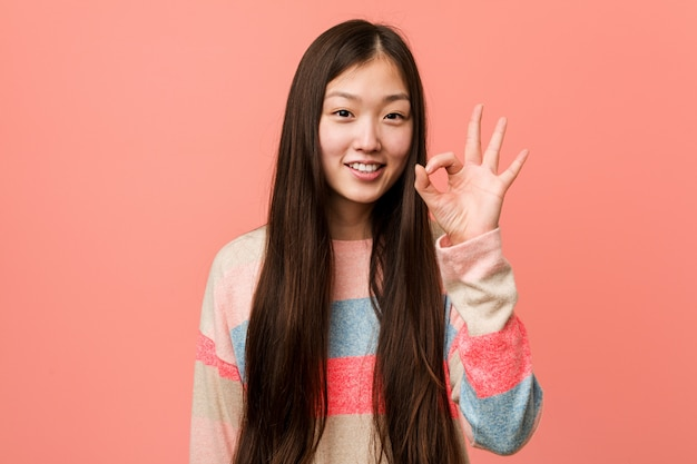 Young cool chinese woman cheerful and confident showing ok gesture.