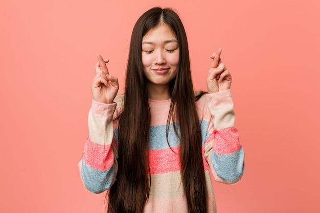 행운을 갖는 젊은 멋진 중국 여자 횡단 손가락