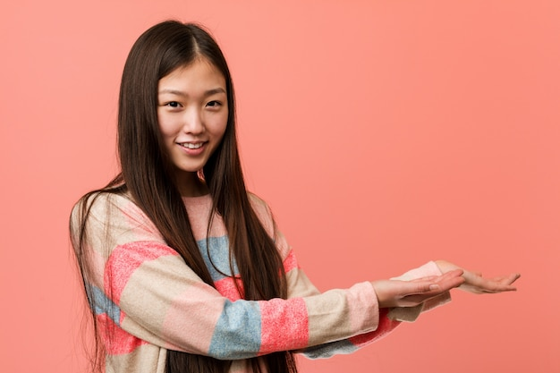 Young cool chinese woman holding a copy space on a palm.