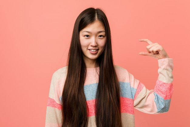 Young cool chinese woman holding something little with forefingers, smiling and confident.