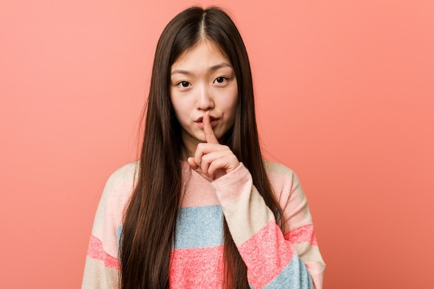 Young cool chinese woman keeping a secret or asking for silence.