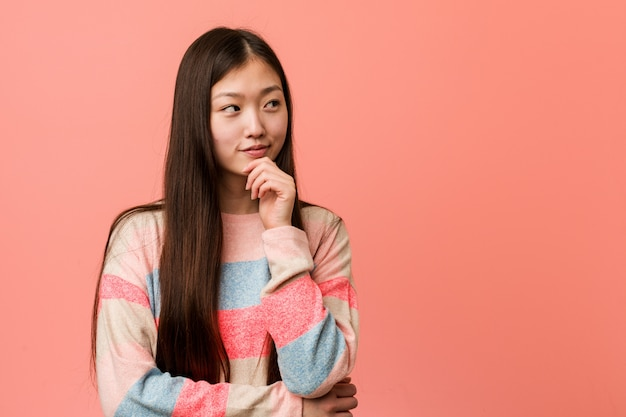 Young cool chinese woman looking sideways with doubtful and skeptical expression.
