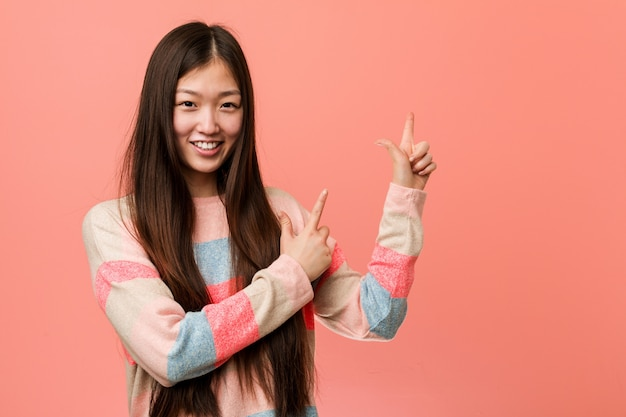 Young cool chinese woman pointing with forefingers to a copy space, expressing excitement and desire.