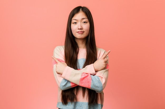 Young cool chinese woman points sideways, is trying to choose between two options.