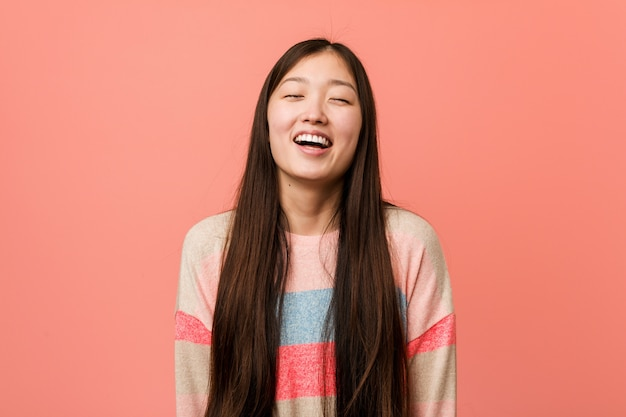 Young cool chinese woman relaxed and happy laughing, neck stretched showing teeth.