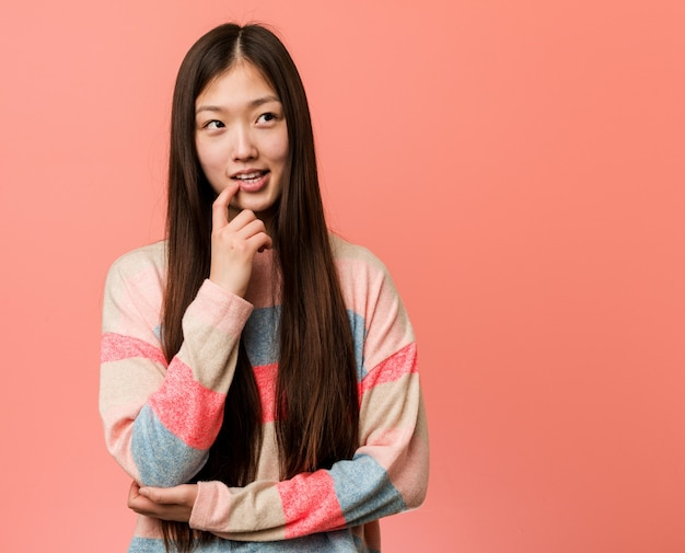 Young cool chinese woman relaxed thinking about something looking at a copy space.