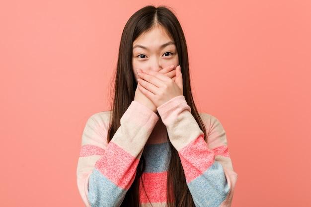 Молодая классная китаянка шокировала рот руками.