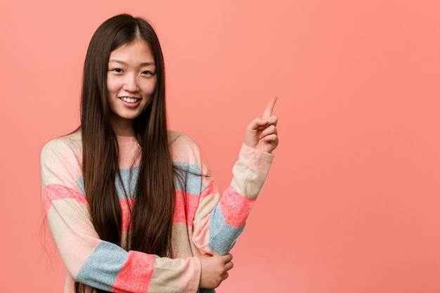 Young cool chinese woman smiling cheerfully pointing with forefinger away.