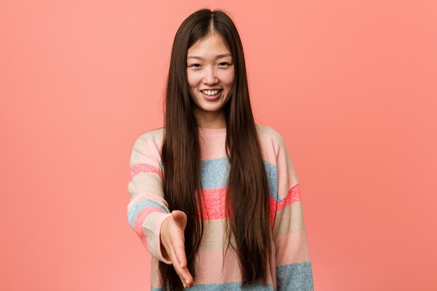 Young cool chinese woman stretching hand at camera in greeting gesture.