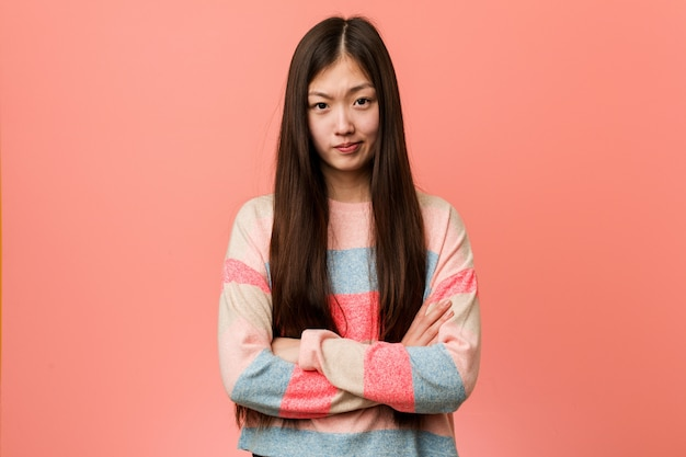 Young cool chinese woman unhappy looking in camera with sarcastic expression.
