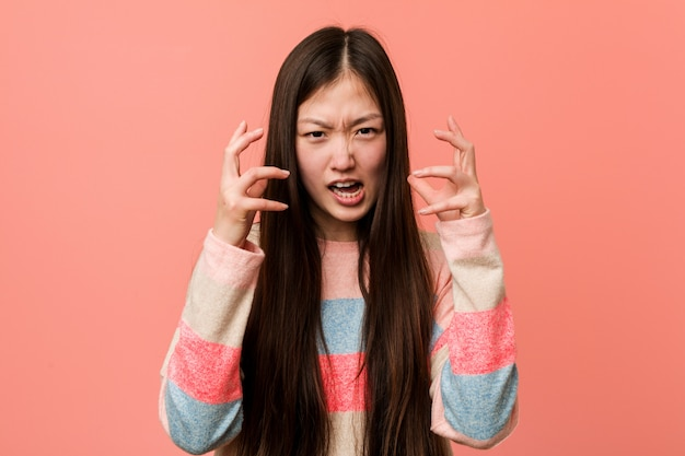 Young cool chinese woman upset screaming with tense hands.