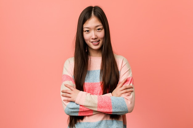 Молодая спокойная китаянка, которая чувствует себя уверенно, скрещивая руки с решимостью.