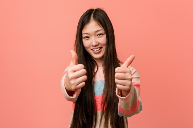 Young cool chinese woman with thumbs ups, cheers about something, support and respect concept.