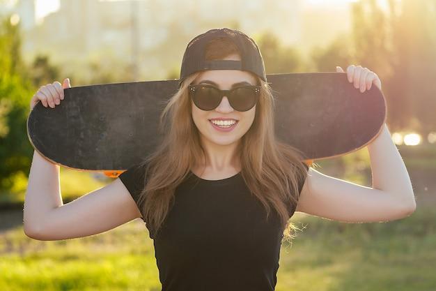 Молодая классная девушка держит скейтборд в скейтпарке.