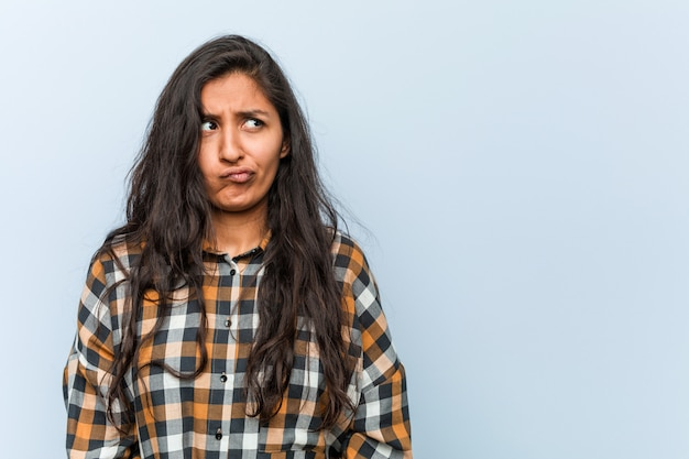 Young cool indian woman confused, feels doubtful and unsure.