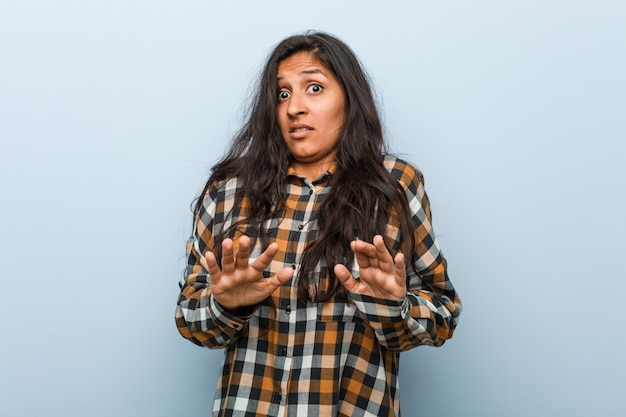 Young cool indian woman rejecting someone showing a gesture of disgust.